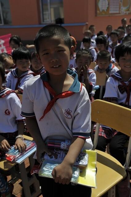 """孩子们拿着由吉林省图书馆赠送的文具,彩笔等""""六一""""儿童节礼物,一个个"""